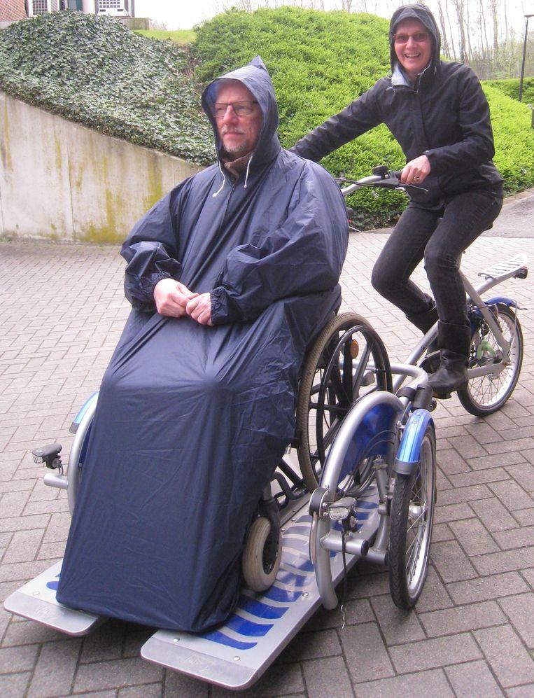 Anne-Mieke en haar partner Luc Neyts mochten in wzc Herdershove in Brugge (die net als wzc Sint-Jozef onder de vleugels van zorggroep Curando valt) al eens een elektrische rolstoel uitproberen. Echtgenoot Luc (die voor alle duidelijkheid geen rolstoelpatiënt is) poseert in de rolstoel met een rolstoelregenponcho.