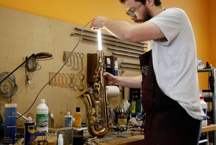 De Belgische instrumentmaker Nicolas Talbot inspecteert een saxofoon in zijn werkplaats in Brussel. Foto Francois Lenoir