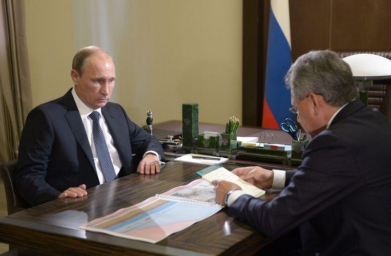 De Russische president Poetin en defensieminister Sergei Sjojgoe in een tv-uitzending na de aanval met raketten op IS in Syrië. Beeld epa