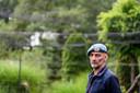 Leon Kok in zijn tuin met een net erboven. Hij houdt er karpers in een door hem zelf aangelegde vijver.