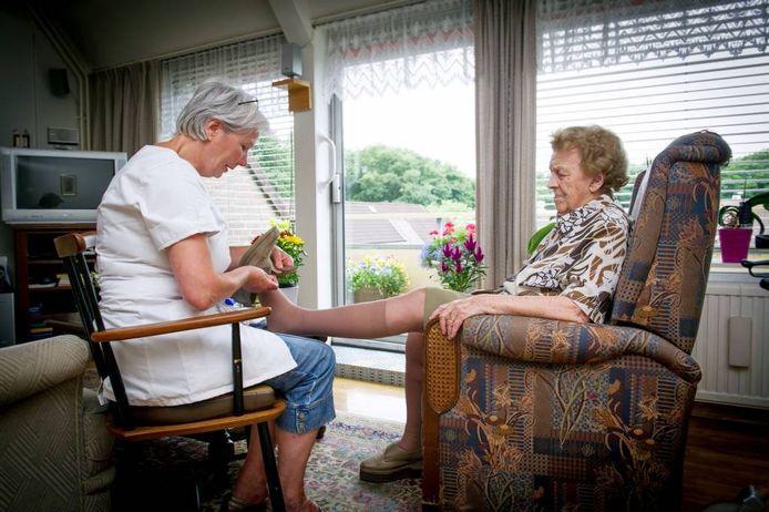 Een wijkverpleegkundige helpt een thuiswonende oudere bij het aantrekken van steunkousen.