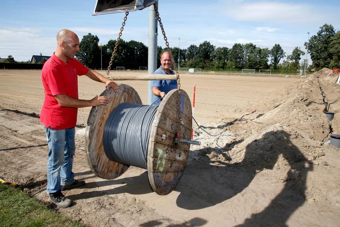 Tim (links) en André zorgen dat de bekabbeling voor de verlichting op het veld waar het kunstgras komt van VV Hontenisse.