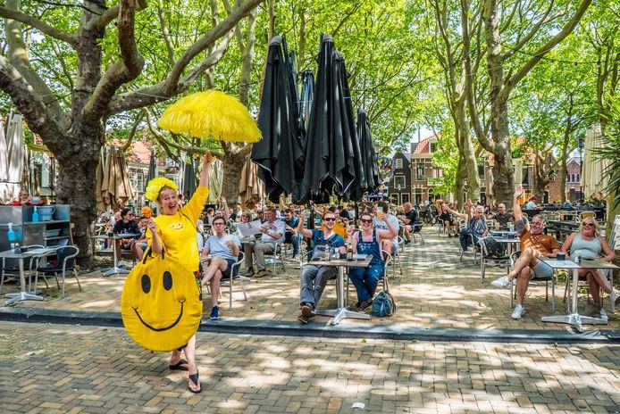 De terrassen op de Beestenmarkt worden breed lachend voor heropend verklaard door 'Madam Delft' Barbara van Gelder.