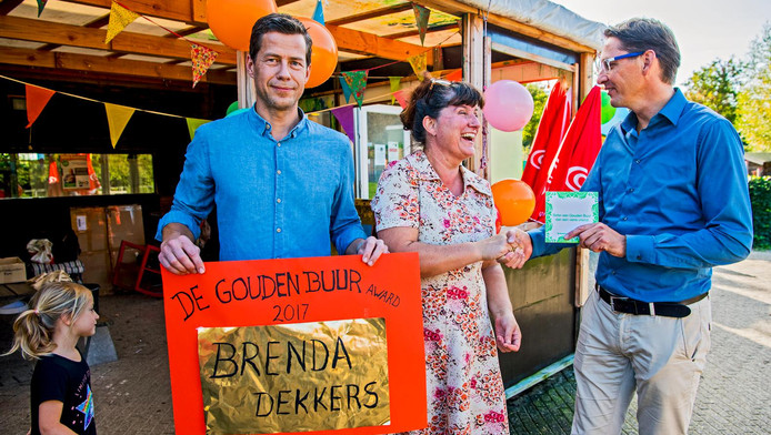 Brenda Dekkers is overdonderd als ze uit handen van wethouder Joost Eerdmans (rechts)¿en de directeur van Nextdoor de Gouden Buur Award krijgt als beste buurvrouw van Zuid-Holland.