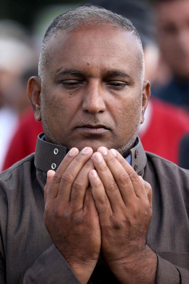 Een man bidt tijdens de herdenkingsdienst.