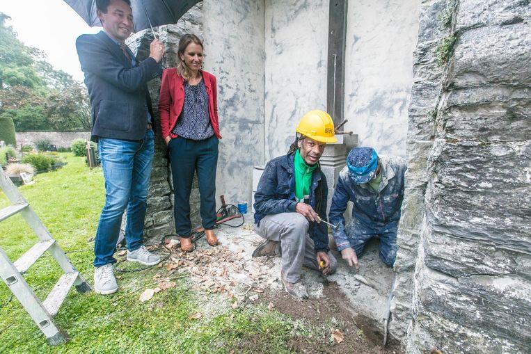 Bernard Cnockaert van Compaan en schepen Sofie Bracke kijken toe hoe Tom en Antoon de kapel renoveren.