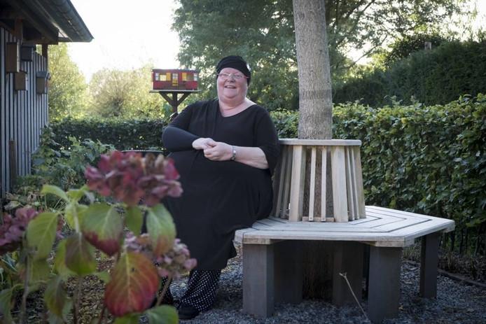 Wilma Demon-de Koning in haar achtertuin, bij de (levens)boom van haar in 2009 overleden man. foto erik van 't hullenaar