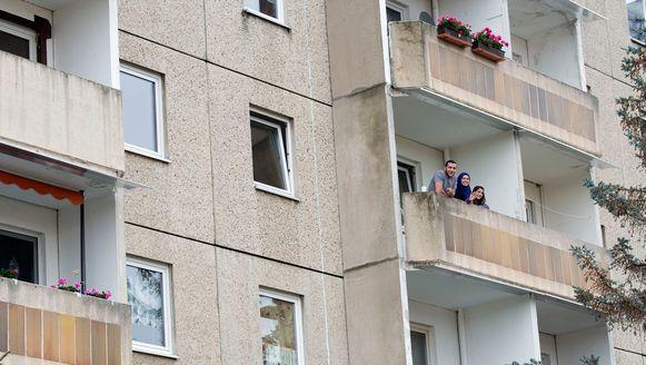 Syrische vluchtelingen op het balkon van hun appartementje in de Duitse stad Zwickau.