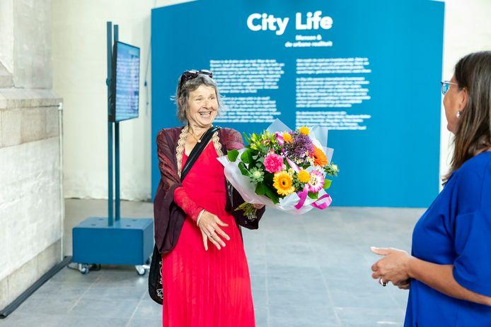Museum Arnhem (rechts op de rug gezien directeur Saskia Bak) viert de heropening met een bloemetje voor de bezoekers.