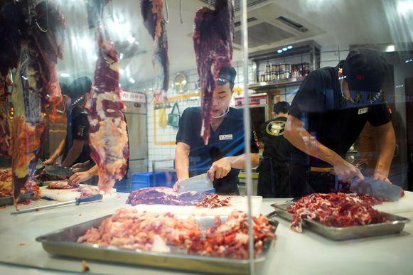 Restaurantmedewerkers snijden het vlees in een restaurant in Shenzhen.