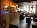 Restaurant OM. Het interieur met opvallende houten bar.