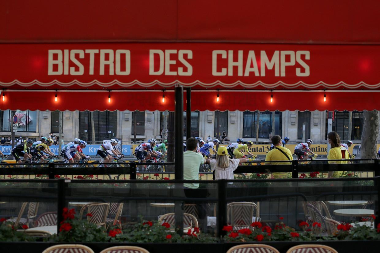Toeschouwers kijken vanaf een terras naar het peleton op de Champs d'Elysees.  Beeld AP