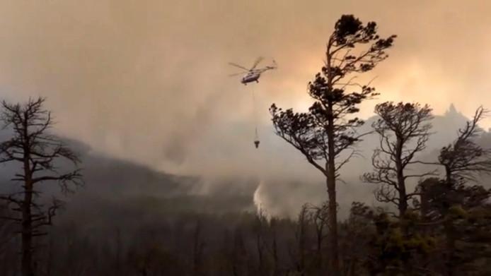 Een blushelikopter haalt bluswater op uit het Baikalmeer om bosbranden in het gebied te blussen (Archiefbeeld)