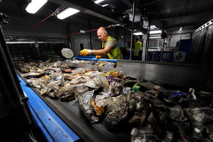 Een medewerker van Omrin in Friesland sorteert plastic op een van de lopende banden in het bedrijf.