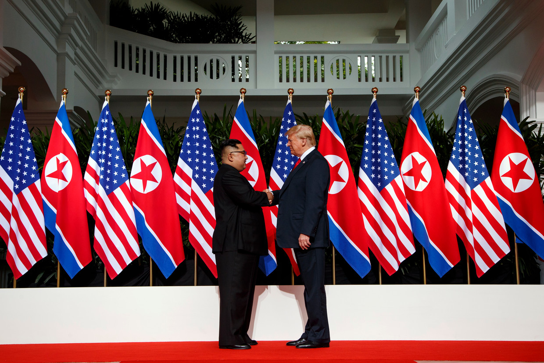 Kim Jong-un en Donald Trump schudden elkaar de hand.