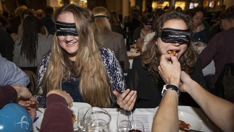 Studenten voeren elkaar tijdens het Blind Eet Diner. Beeld Dingena Mol