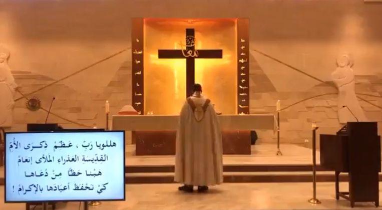 Een priester is bezig met het opnemen van een onlinemis in een kerk... Beeld