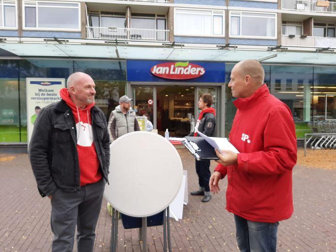 SP-lid Ronald Jansen (r) haalt in de Arnhemse wijk Malburgen-West handtekeningen op van mensen die het verzoek voor een referendum over het afvalbeleid willen steunen.