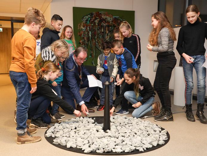 Burgemeester Jan Lonink maakt samen met schoolkinderen het Holocaust-monument compleet.