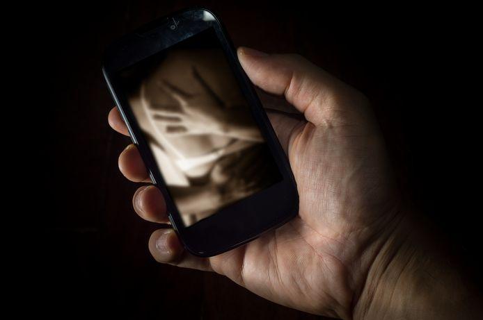 Man kijkt naar intieme foto op zijn telefoon, foto ter illustratie.