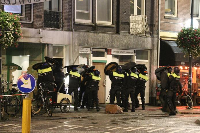 Politie valt het gekraakte pand aan de Burgemeester Reigerstraat binnen.