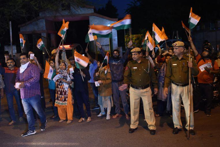 Demonstranten zwaaiend met de Indiase vlag en politieagenten drommen samen voor de gevangenis van Tihar waar de verkrachters werden geëxecuteerd.