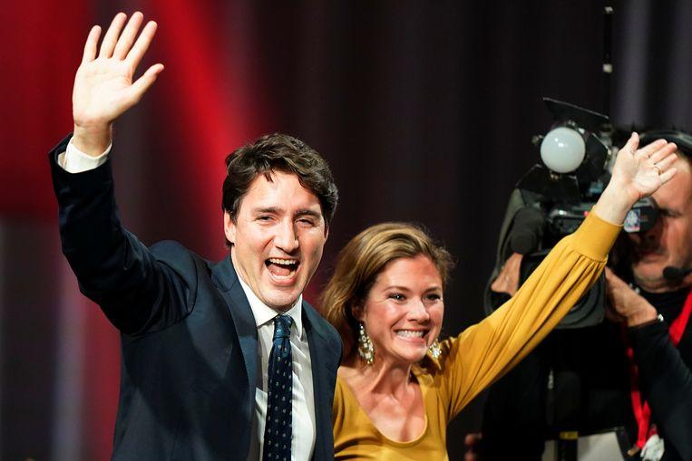 Justin Trudeau en zijn echtgenote Sophie zwaaien naar aanhangers nadat de verkiezingsuitslag heeft uitgewezen dat hij mogelijk opnieuw als premier van Canada aan de slag kan.  Beeld REUTERS