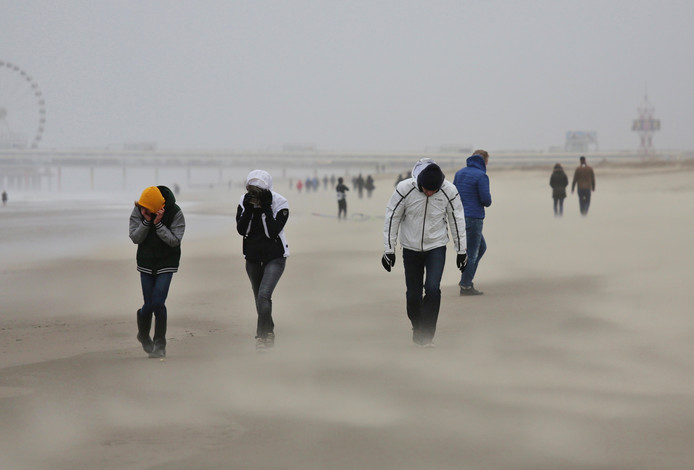 Mensen op het strand bij Scheveningen vechten tegen de storm.
