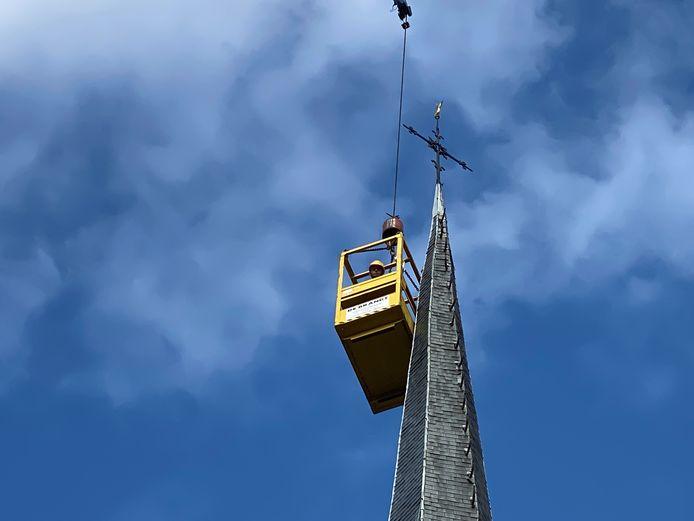 Bengelend in een bakje controleren werkmannen de leistenen van de torenspits