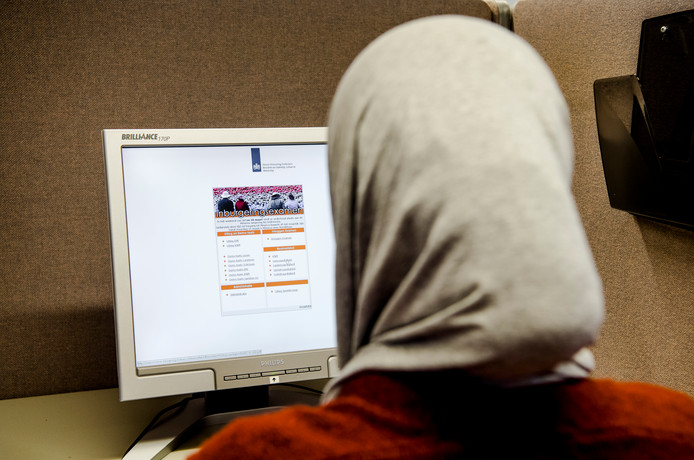 Een vrouw doet inburgeringsexamen op een toetslocatie van Dienst Uitvoering Onderwijs (DUO).