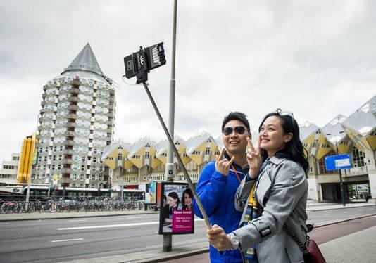 Toeristen maken een selfie bij Rotterdam-Blaak.