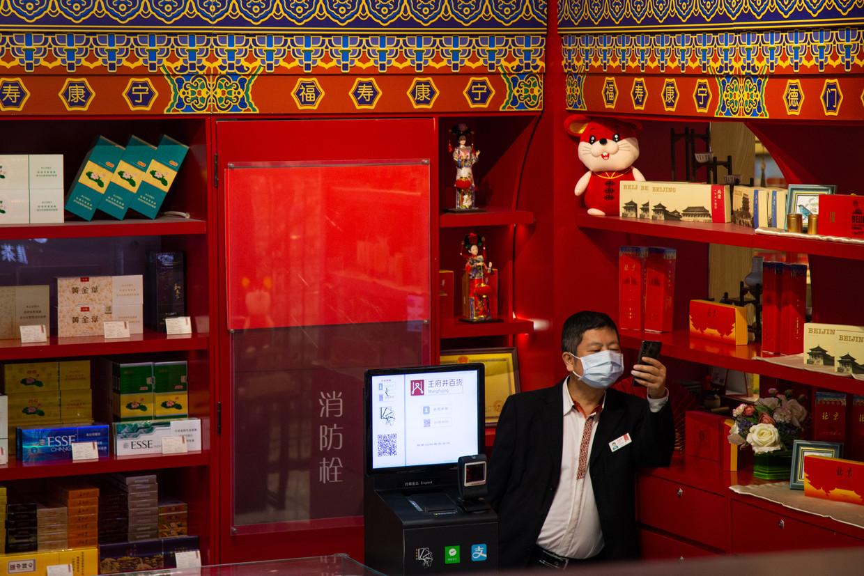 Een winkelier in Peking draagt een masker om besmetting met het wuhanvirus te voorkomen.