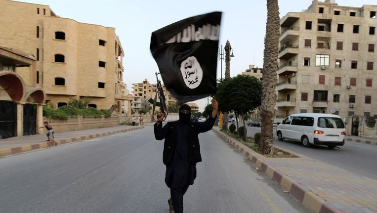Een man zwaait met de vlag van ISIS in de Syrische stad Raqqa. Beeld reuters