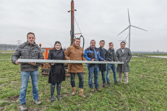 Robèrt Hopmans, Miyo Shiino, André Kempenaars, Chris Hopmans, Qi Shi, Han Hopmans en Udo Weggeman met de eerste paal van Zonnepark Rilland.