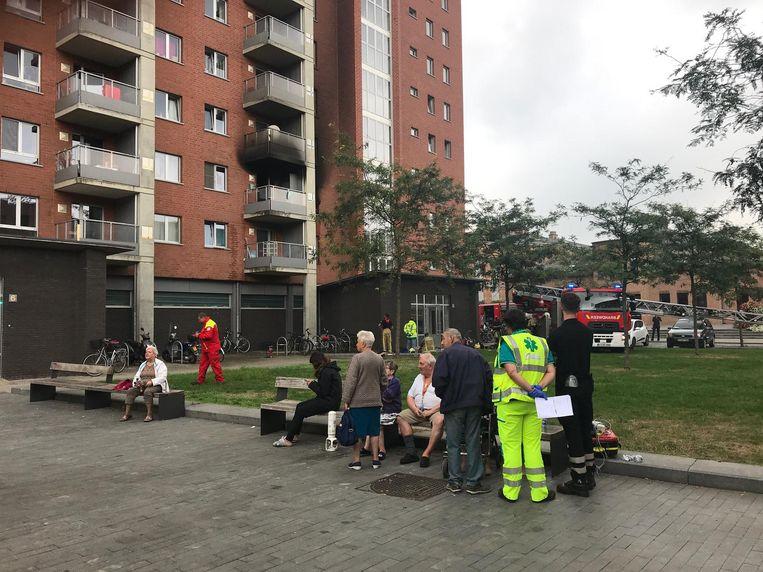 De bewoners staan allemaal buiten terwijl de hulpdiensten zich over hen ontfermen. Het derde balkon rechts is helemaal zwartgeblakerd door de keukenbrand die in het appartement eronder ontstond.
