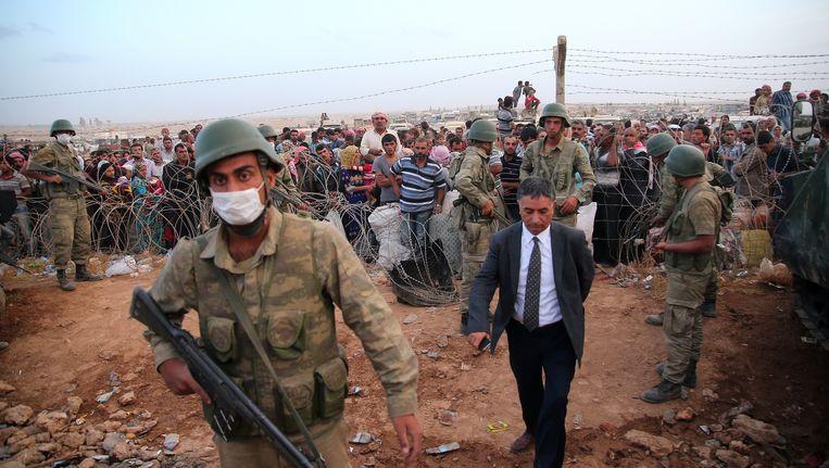 Turkse soldaten bewaken Syrische vluchtelingen die net de grens zijn overgestoken op de vlucht voor het geweld van IS.