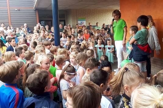 Astrid de Schutter, de directeur van de school, en leerlingen bij onthullen van eigen kunstwerk bij 10-jarig jubileum van basisschool De Wending. Foto Alfred de Bruin