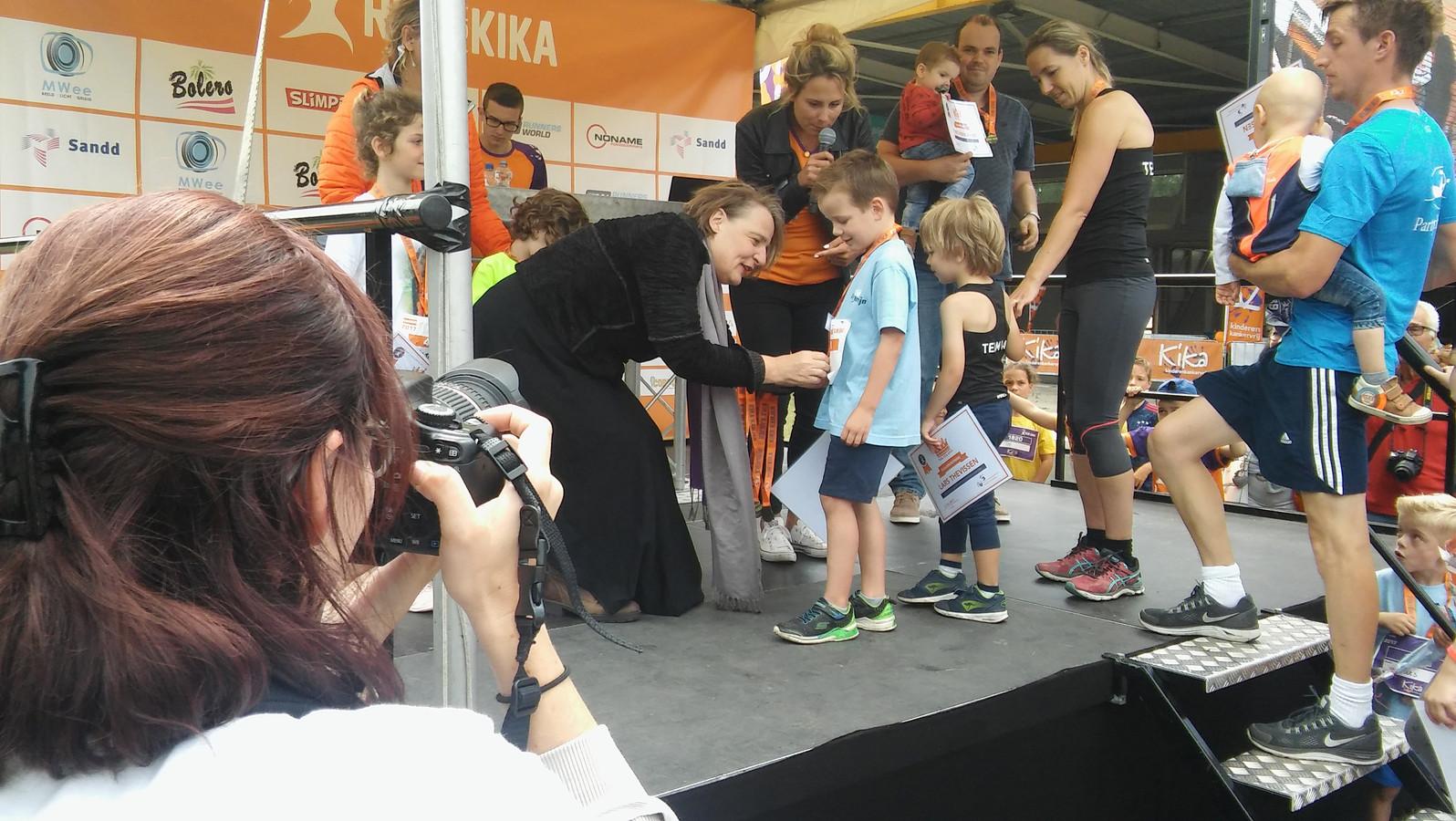 Merijn (6) krijgt van wethouder Mary-Ann Schreurs de medaille en oorkonde tijdens de Kanjerkroning bij de Run fot KiKa in Eindhoven.