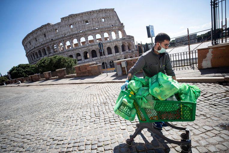 Een man voor het verlaten Colosseum in Rome.  Beeld EPA