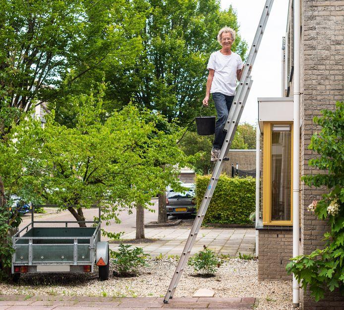 Yogaleraar Wim van Nimwegen geeft de buitenkant van zijn huis een opknapbeurt. ,,Ik dacht: goh, wat is die regenpijp vies. Het is misschien wel tien jaar geleden dat ik hem schoongemaakt had.''