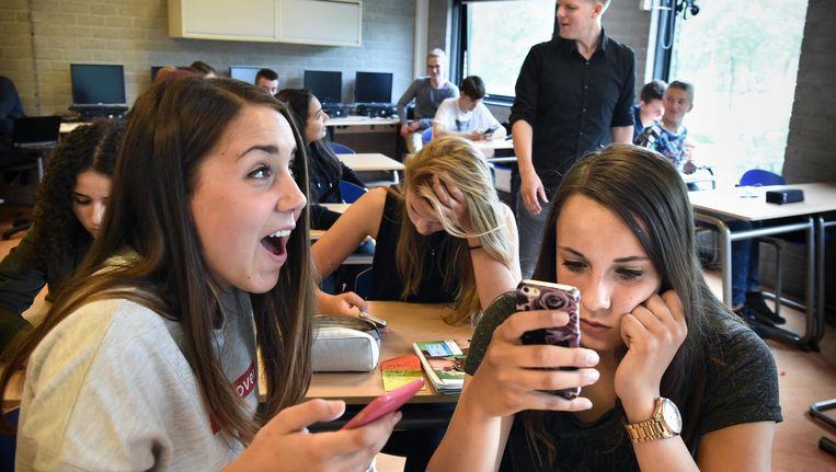 Leerlingen van een VMBO in Vianen testen een nieuwe applicatie met hun telefoon. Beeld Marcel van den Bergh / de Volkskrant