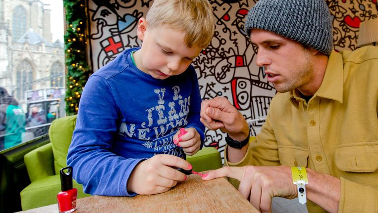 De 6-jarige Tijn lakt de nagels van windsurfer Dorian van Rijsselberghe. Beeld anp