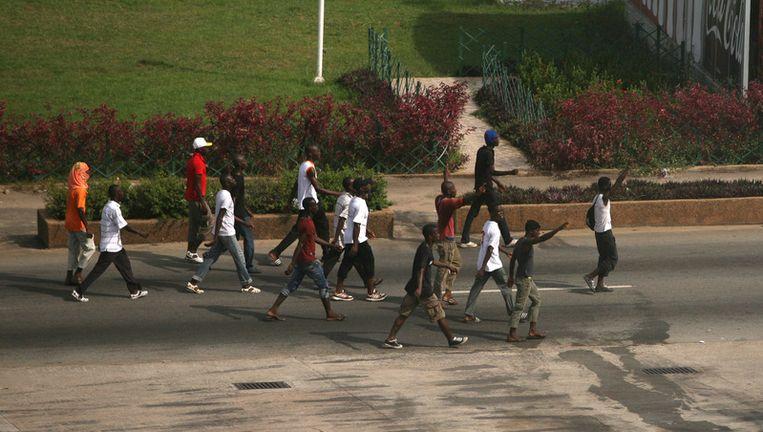 Leden van een jongerenmilitie loyaal in Gbagbo lopen door Abidjan. Beeld ap