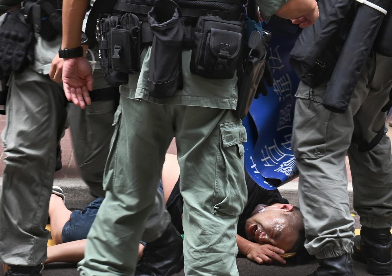 Een demonstrant is aangehouden in Hongkong op 1 juli, de 23ste verjaardag van de overdracht van Hongkong aan China. Beeld EPA