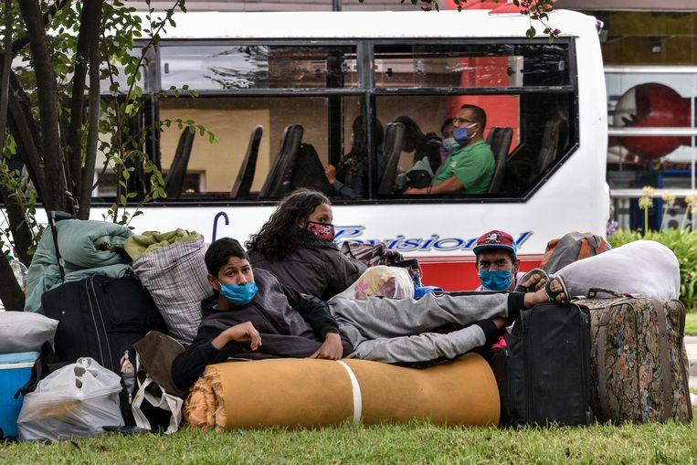 Dakloze Venezolanen wachten bij het busstation in Bogotá (Colombia) op hulp om naar huis te kunnen terugkeren. Beeld Getty Images