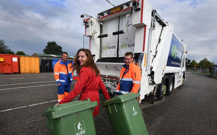Wethouder Hilde de Groot sleept een paar kliko's naar de nieuwe vuilniswagen.