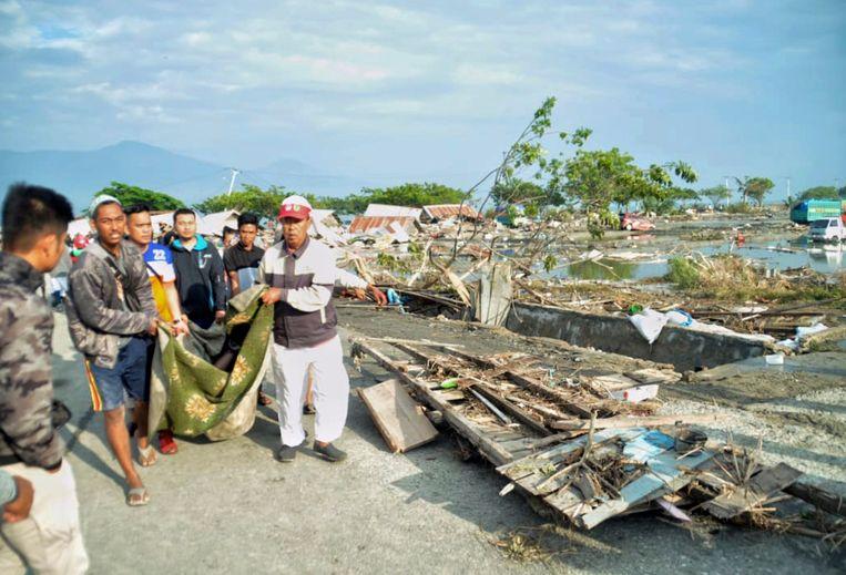 Bewoners dragen het lichaam van een slachtoffer in Palu, de hoofdstad van het Indonesische eiland Sulawesi. Beeld AP