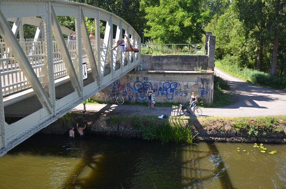 Verkoeling zoeken in stijl: deze jongen springt met een salto van de Spletterenbrug de Moervaart in.