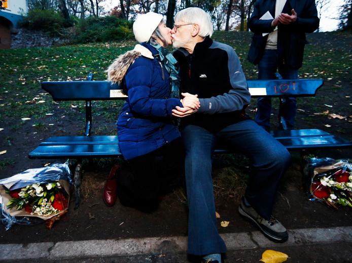 Peggy Vroman en haar echtgenoot kussen elkaar op het bankje waar 80 jaar geleden Leo Vroman zijn vrouw Tineke Sanders  voor het eerst een zoen gaf.