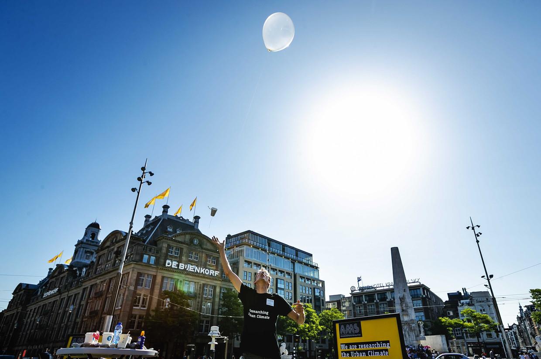 Onderzoekers van Wageningen Universiteit en AMS Institute laten een weerballon op vanaf de Dam. Zo kunnen ze meten tot hoe hoog de hitte in de stad stijgt en hoe groot de vervuiling is. Beeld ANP